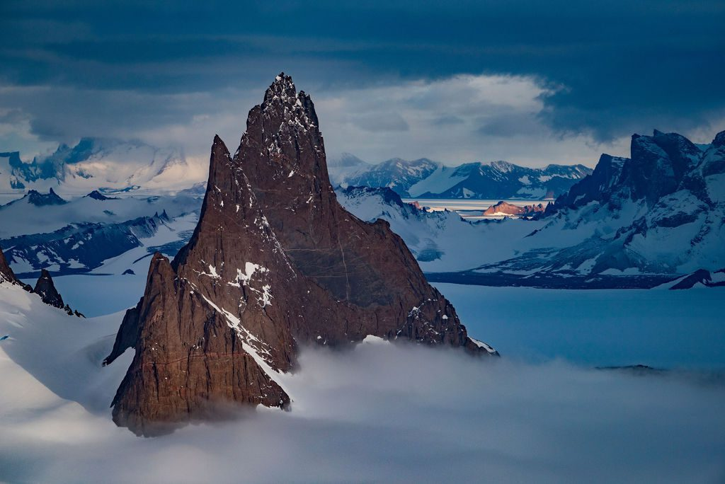 jagged mountains peeking through the clouds in Antarctica