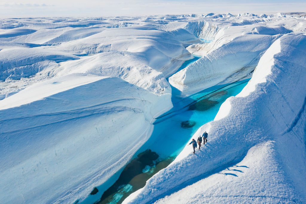 guests hiking along a snowy ridge overlooking aquamarine waters in Antarctica