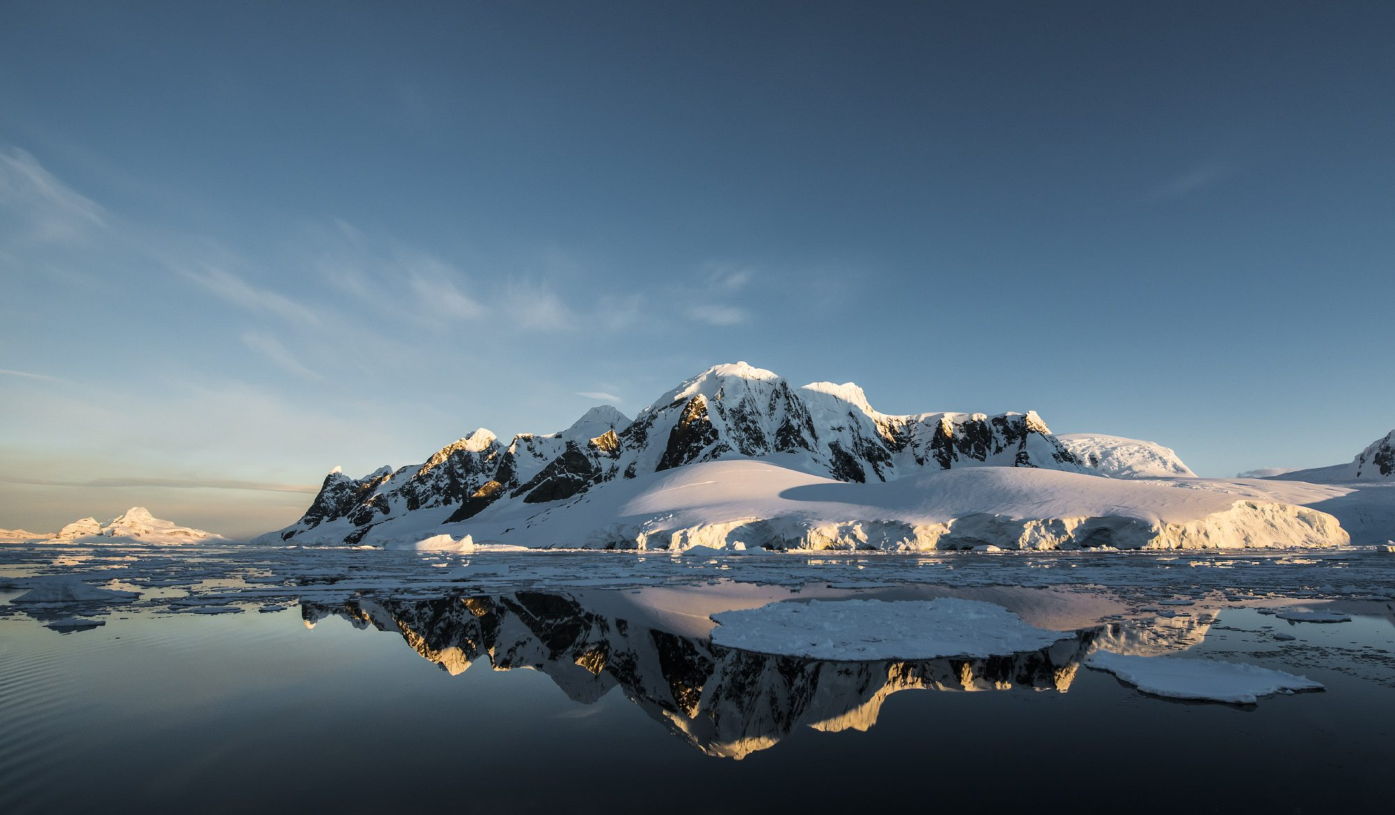 mirror reflection in the icy waters of snow capped mountains on the Antarctic Peninsula