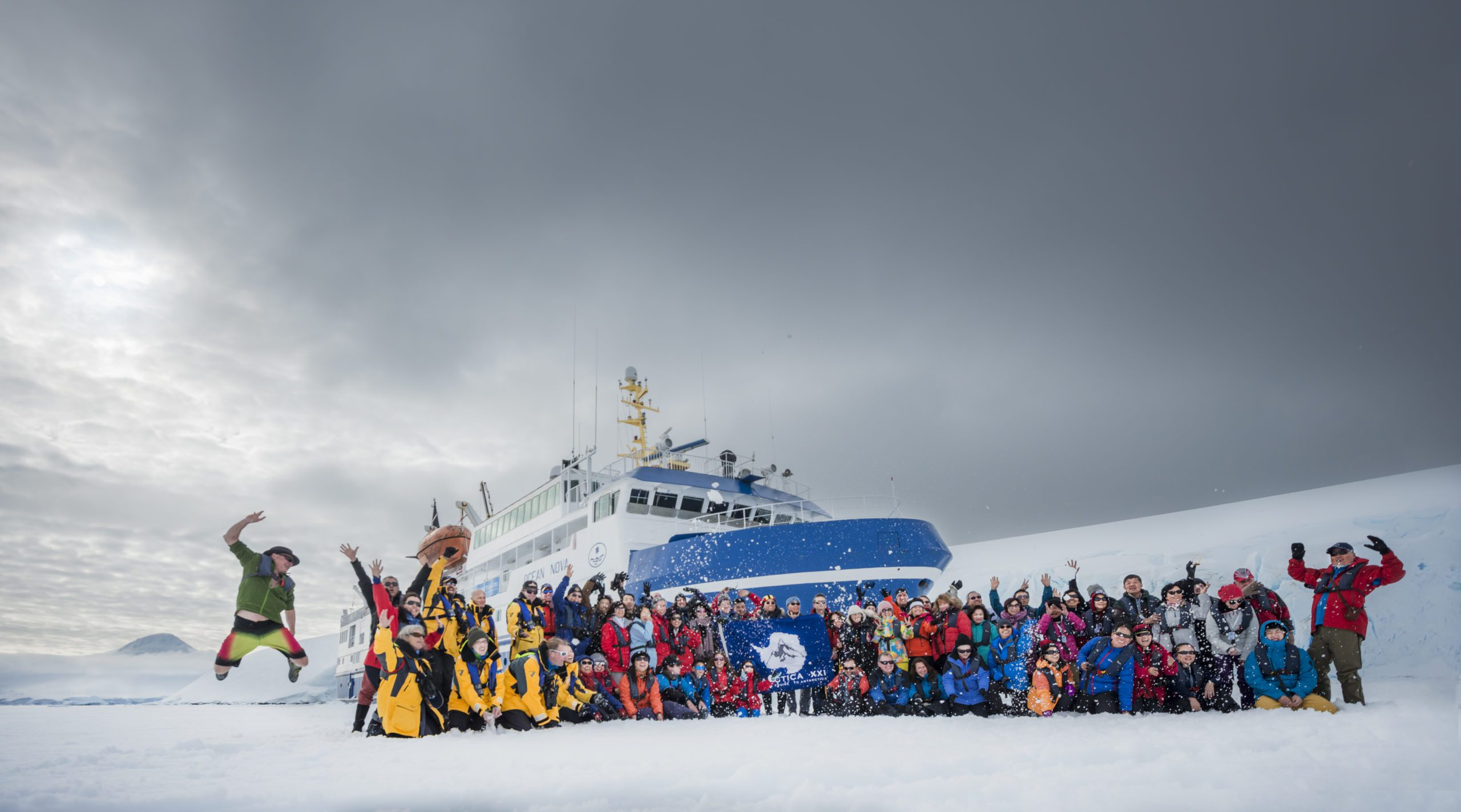 passengers and crew pose in front of their blue and white ice vessel celebrating their arrival to Antarctica