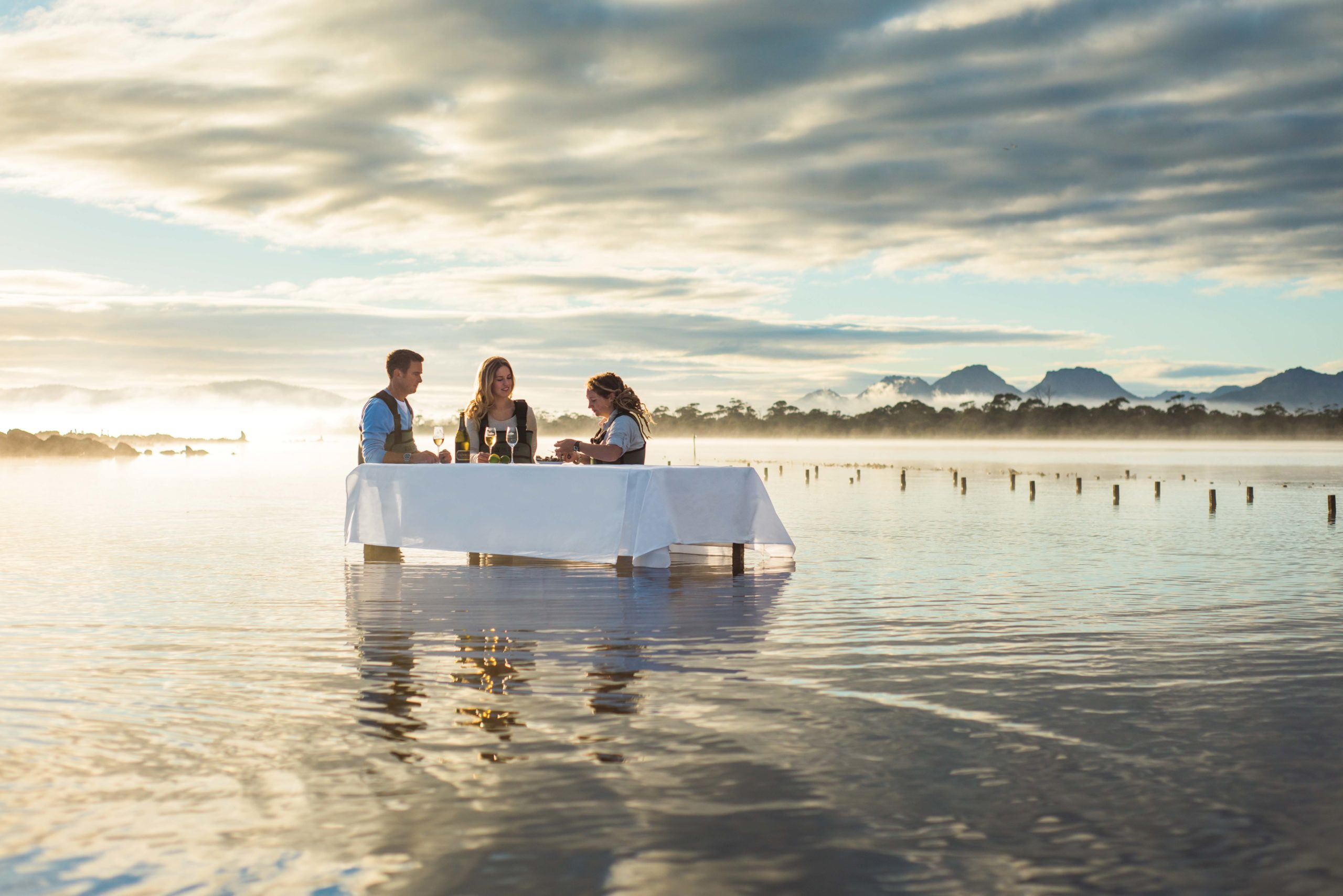 A couple and their guide sit in the shallow water at a table in an oyster farm where they're eating fresh oysters