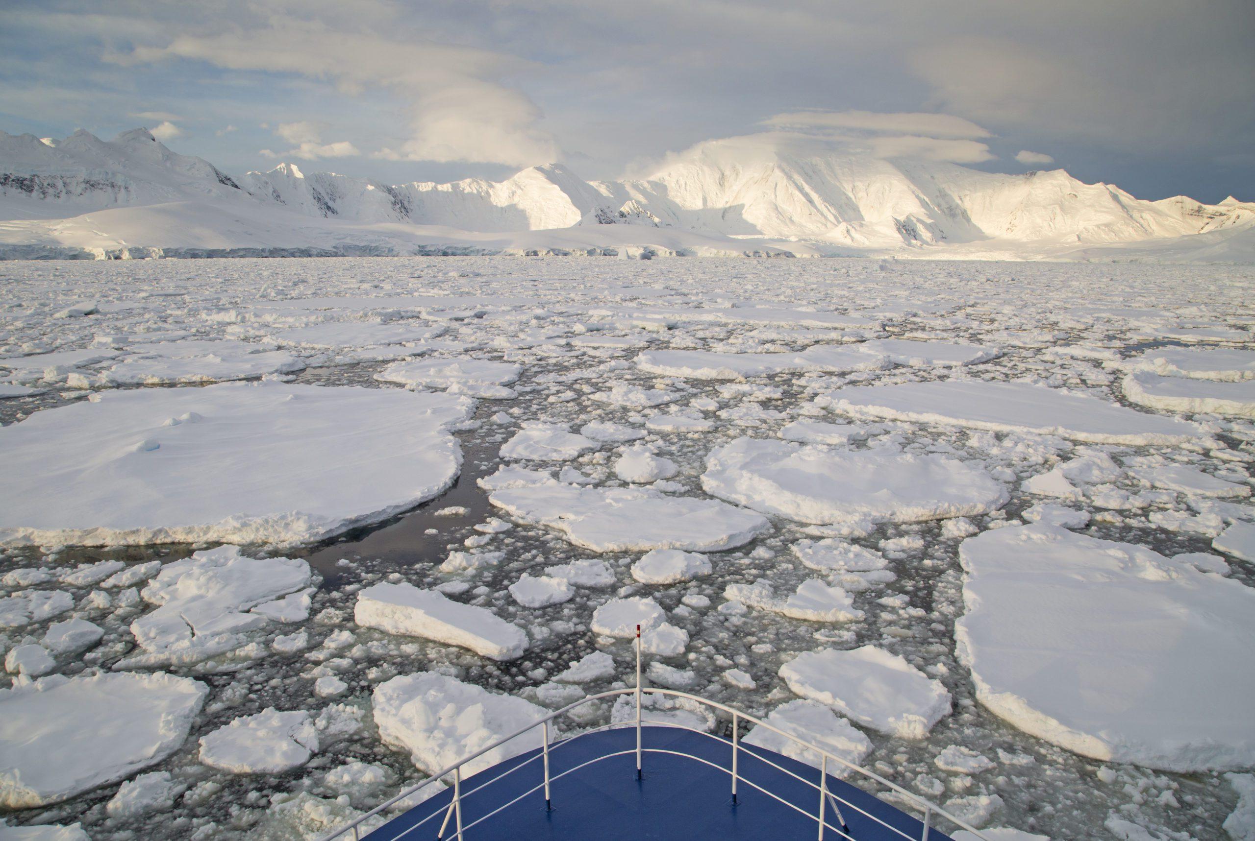 bow of ship breaking through broken up ice in the Antarctic seas