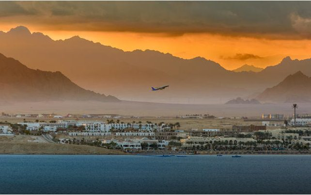 town of Sharm el Sheikh with mountains in the background, waters in foreground, and plane taking off in the sky