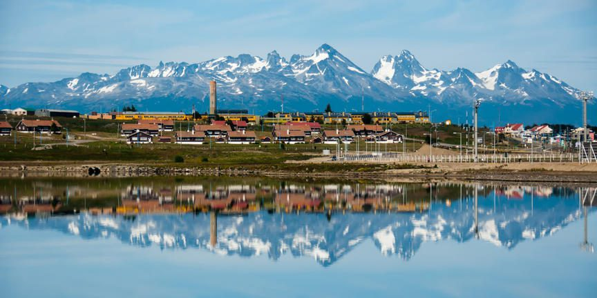 port town sitting on water with stunning mountains behind, showing reflection in ocean