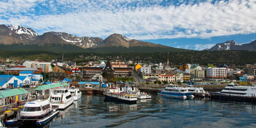 harbour filled with boats, blue skies, clouds and mountains