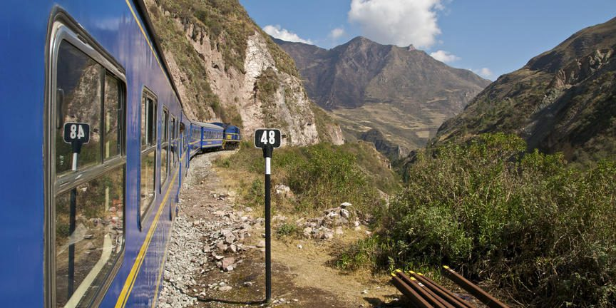 blue train going through the mountains en route Machu Picchu