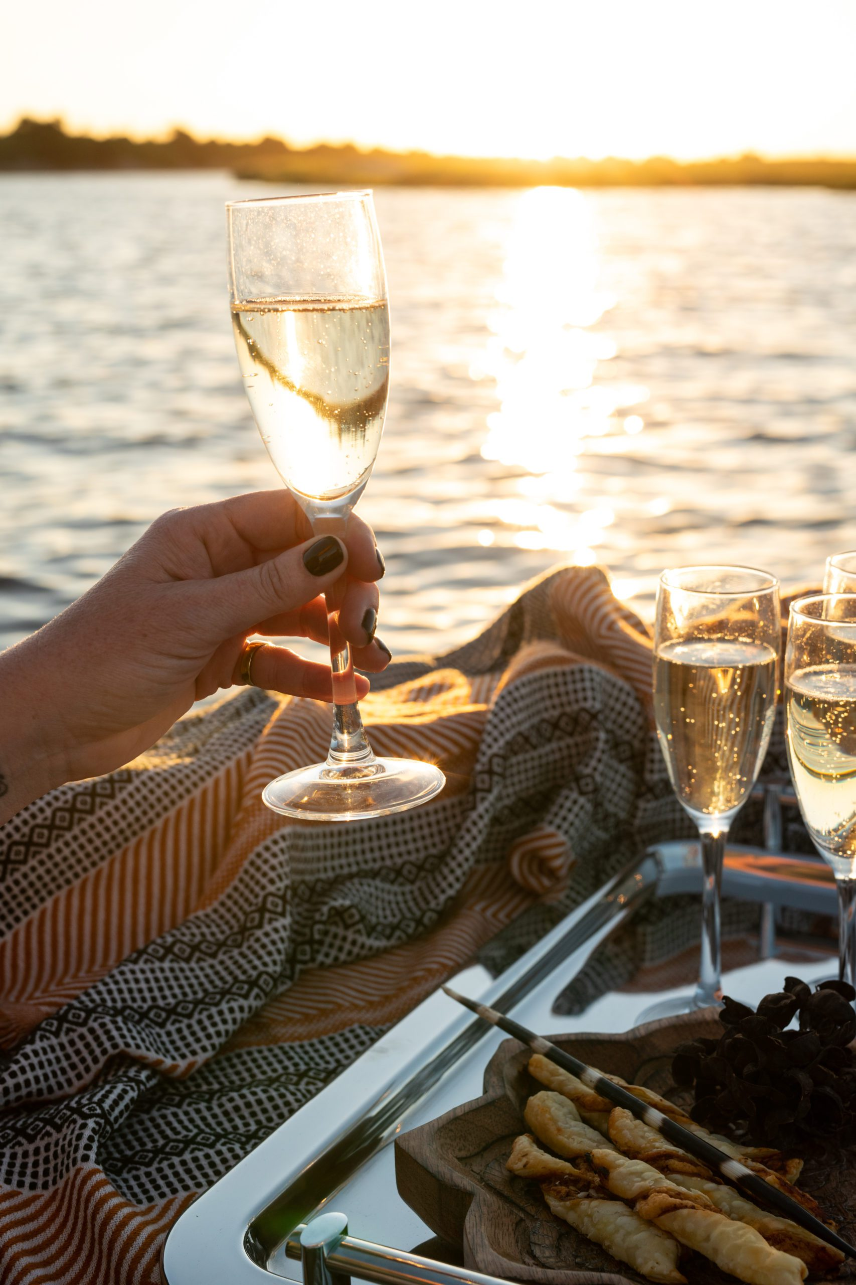 Chobe Princess boat cruise classes of champagne at sunset