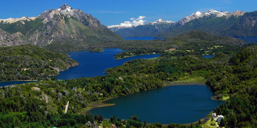 Lakes peppered throughout green landscapes and mountains in the background