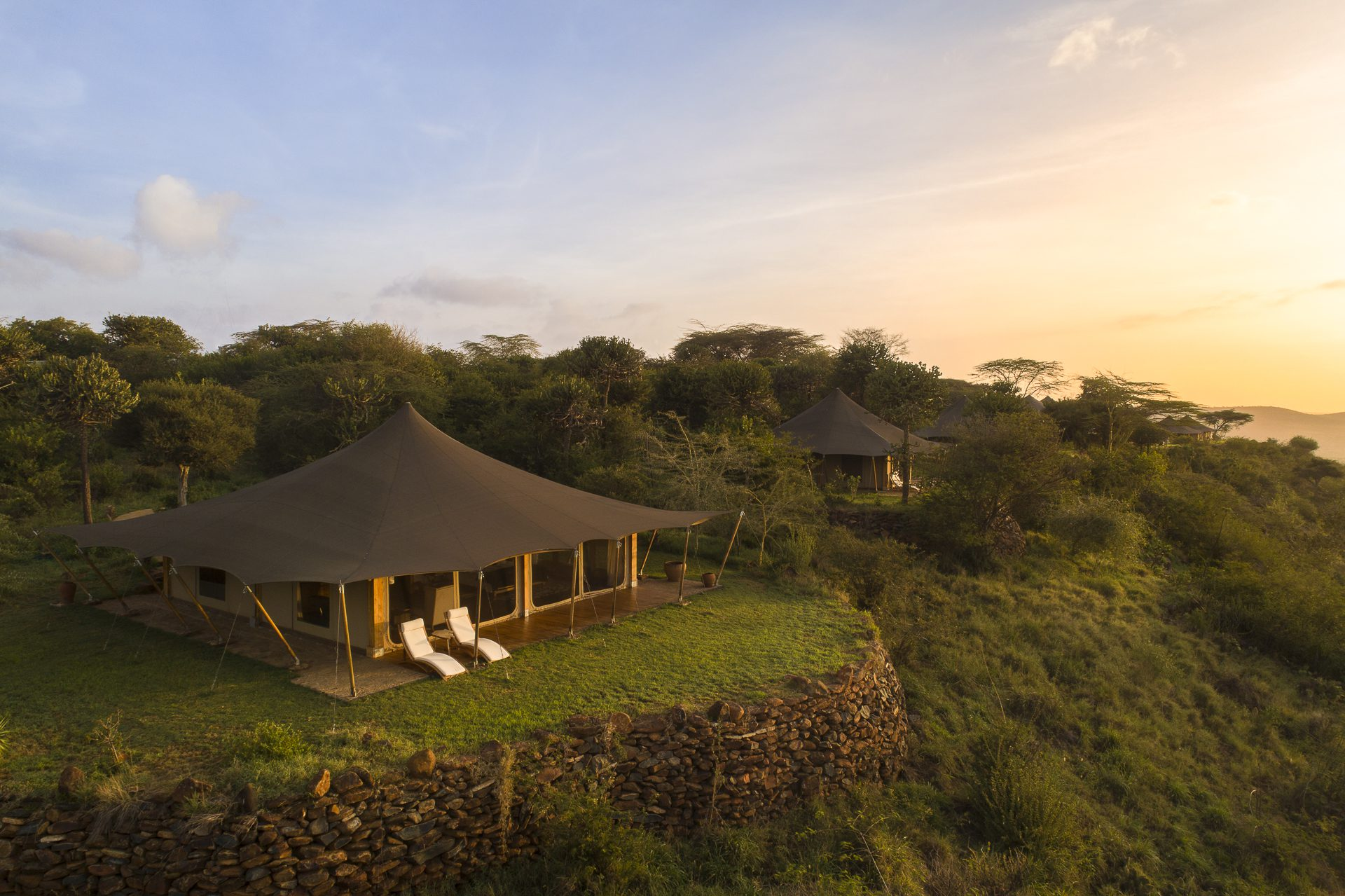 tented safari camp on the edge of a hill at sunrise