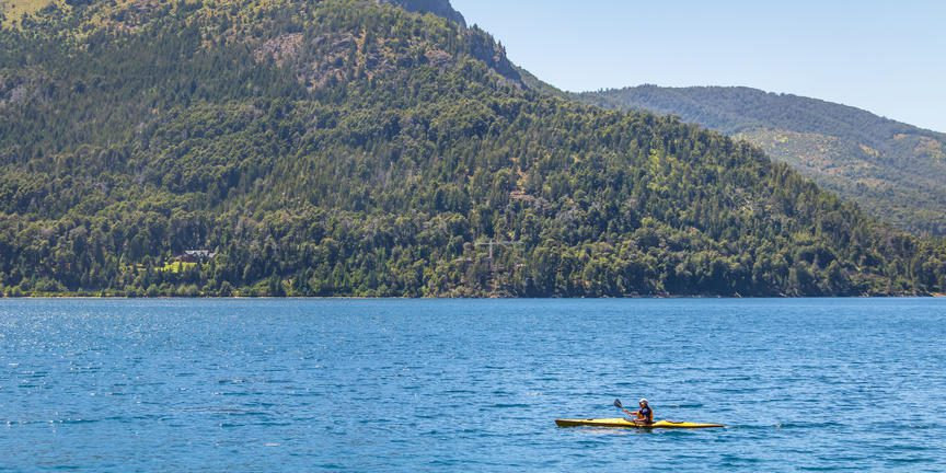 single yellow kayak on the water, with green mountains surrounding