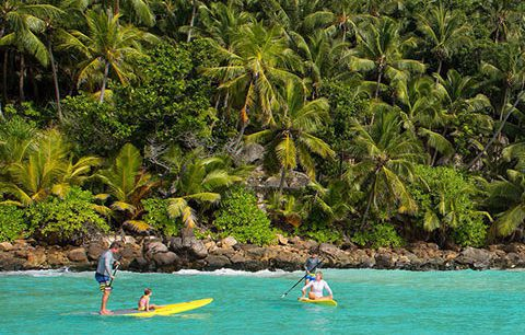 during the best kenya safari people enjoy paddle boarding along the crystal clear waters off North Island, Seychelles
