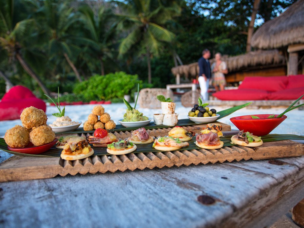 dining spread on the beach with people in background