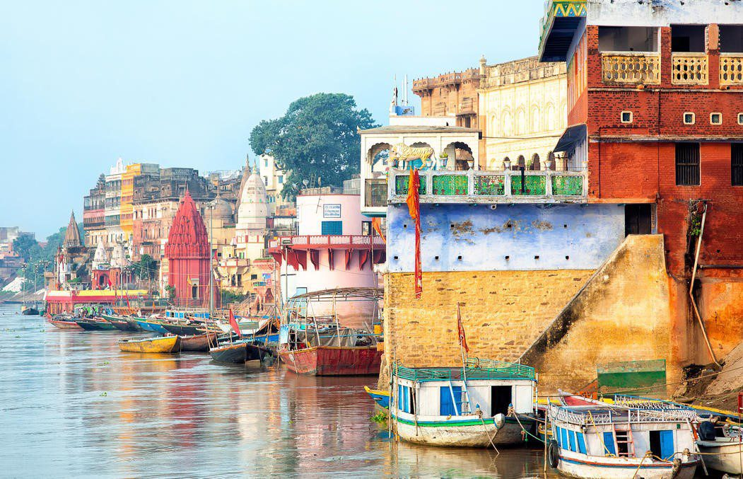 colorful boats and stone buildings on the Ganges River