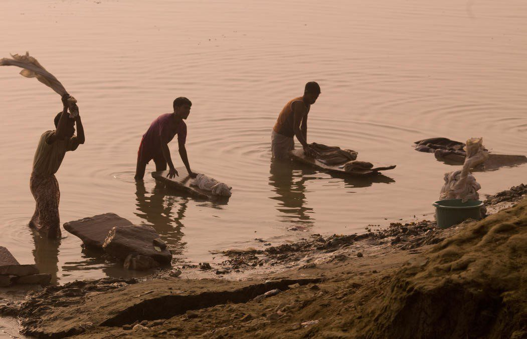 three people washing clothes in the River Ganges