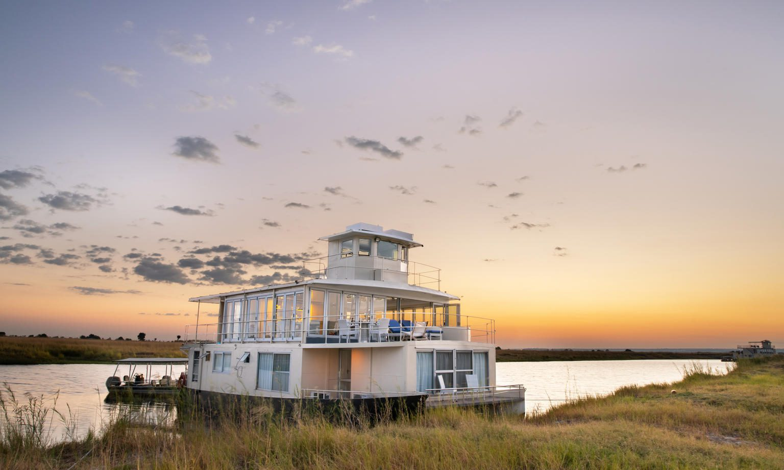 daybreak on the chobe river with a houseboat