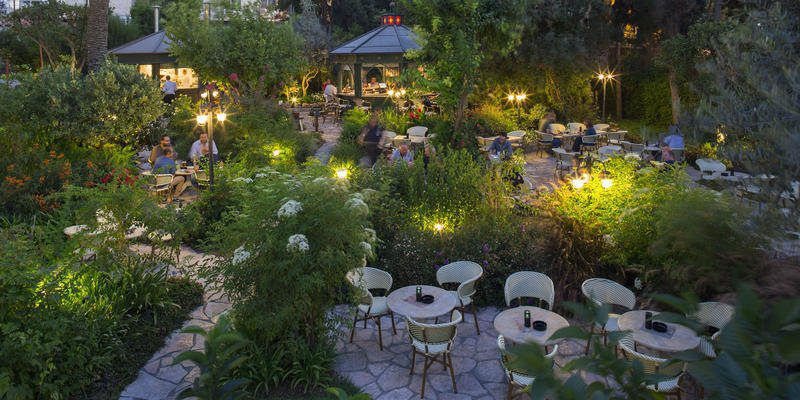 garden with small tables and uplighting