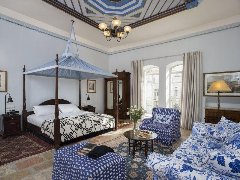 hotel room with white walls and lots of decorative blue couches and ceiling