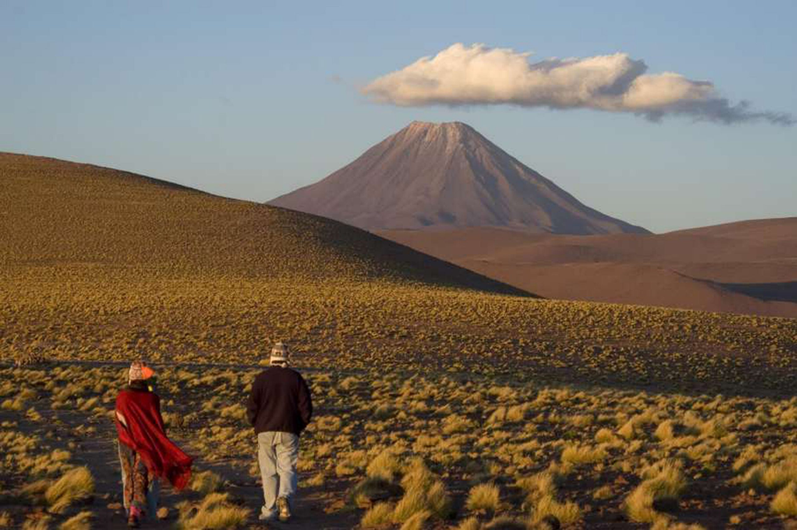 couple walking through desert with volcano