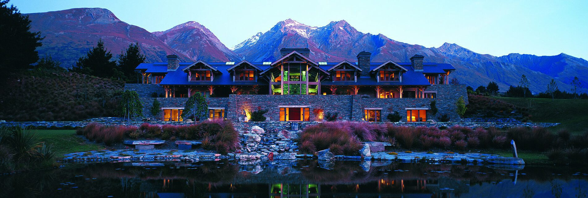 blanket bay lodge in glenorchy with lake wakatipu in front and the mountains behind