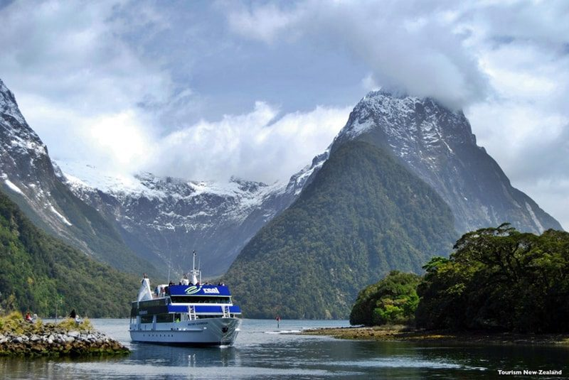 boat cruising through the fjords of milford sound, new zealand