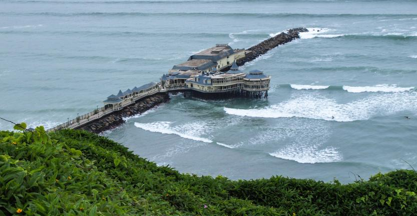 Lone jetty with crashing waves and green cliffs