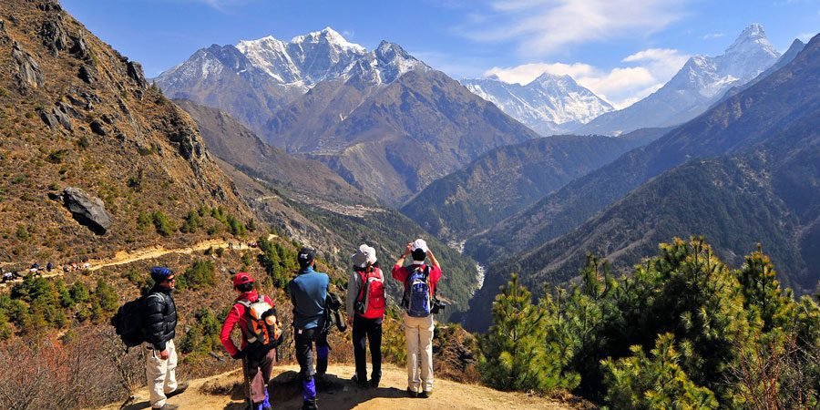 hikers stopping to admire the view while trekking in Nepal