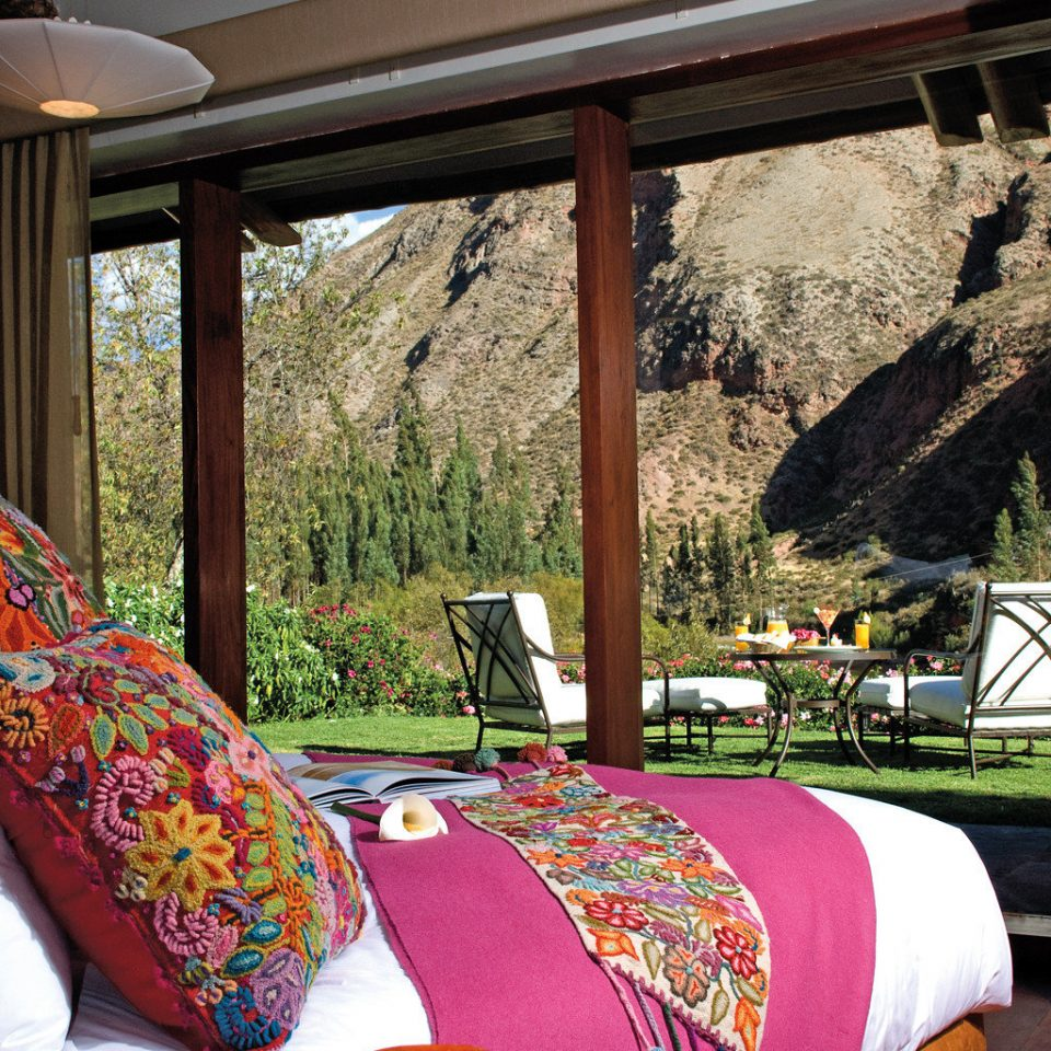 Peru tour bedroom with bright pink bed spread and floral pillows looking out to a grassy courtyard on luxury safari