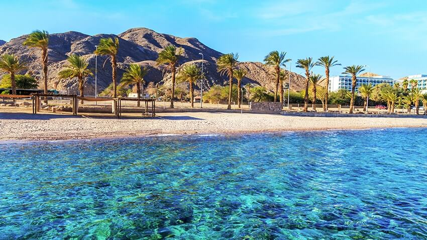 transparent water in Eilat with beach and mountains