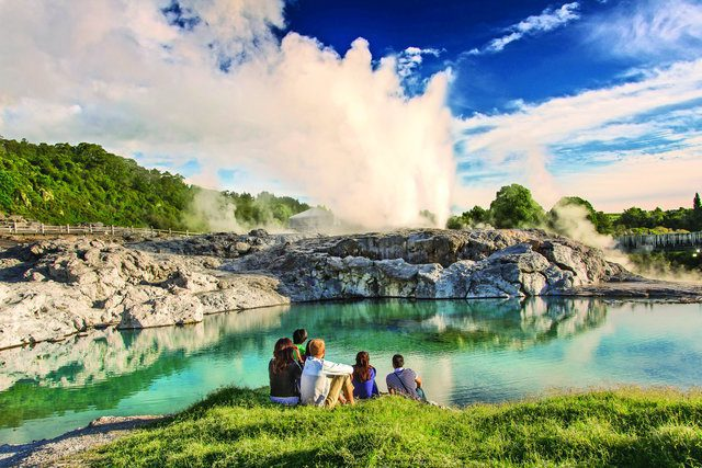 family sitting beside an aqua body of water watching a geyser erupt on New Zealand tour