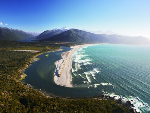 aerial view over the coast of new zealand showing turquoise water and green forests beside mountains on New Zealand's South Island tour