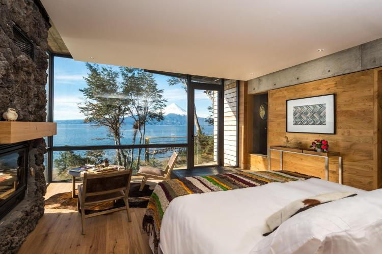 bedroom with wood panels and glass window looking out to water on this Chile holiday