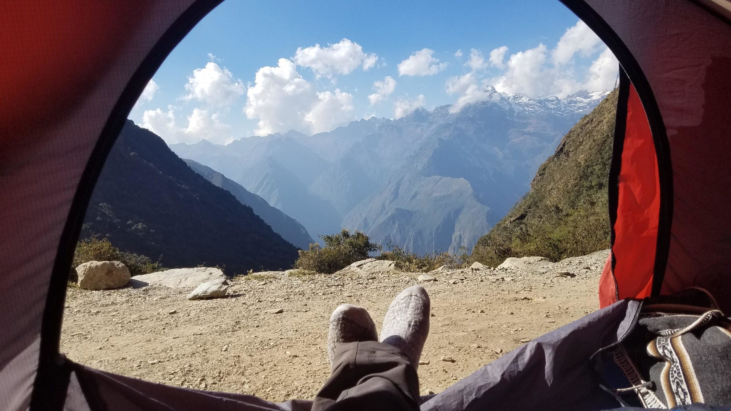 view from a dome tent of crossed feet and views looking out and down the valley