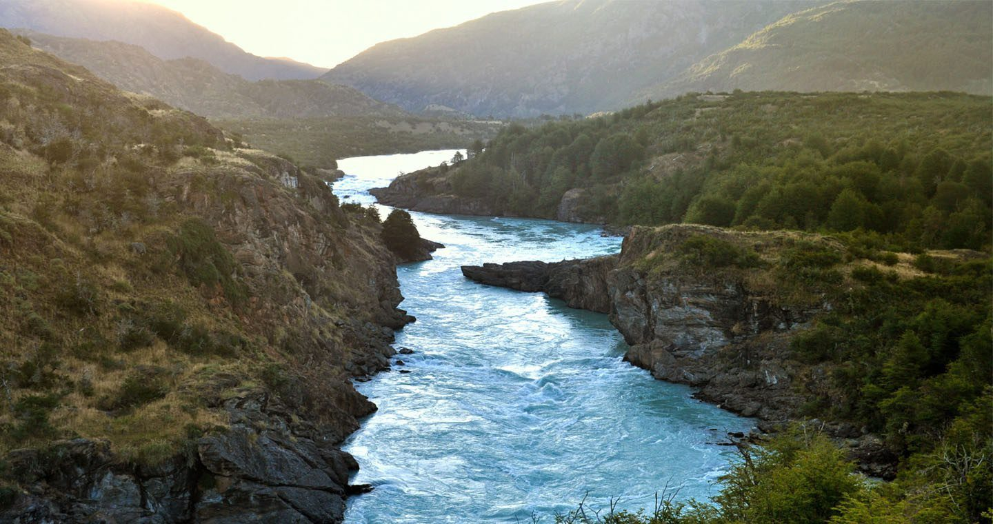 blue river snaking through a valley surrounded by trees and mountains on this Chile tour