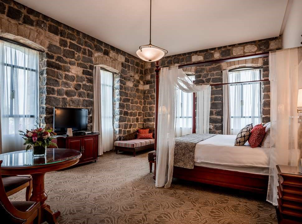 Scots hotel room with exposed brick walls and four poster bed on Israel holiday