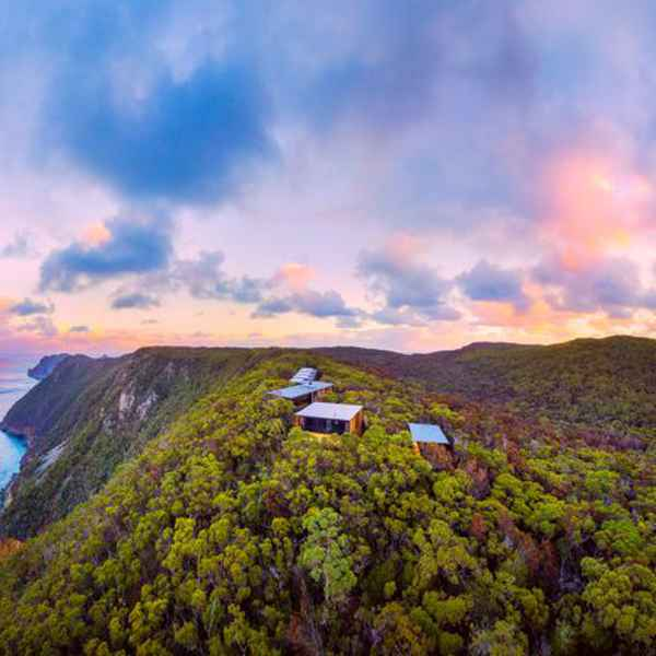 lodges at the edge of a cliff overlooking the ocean at sunset on the three capes walk, tasmania