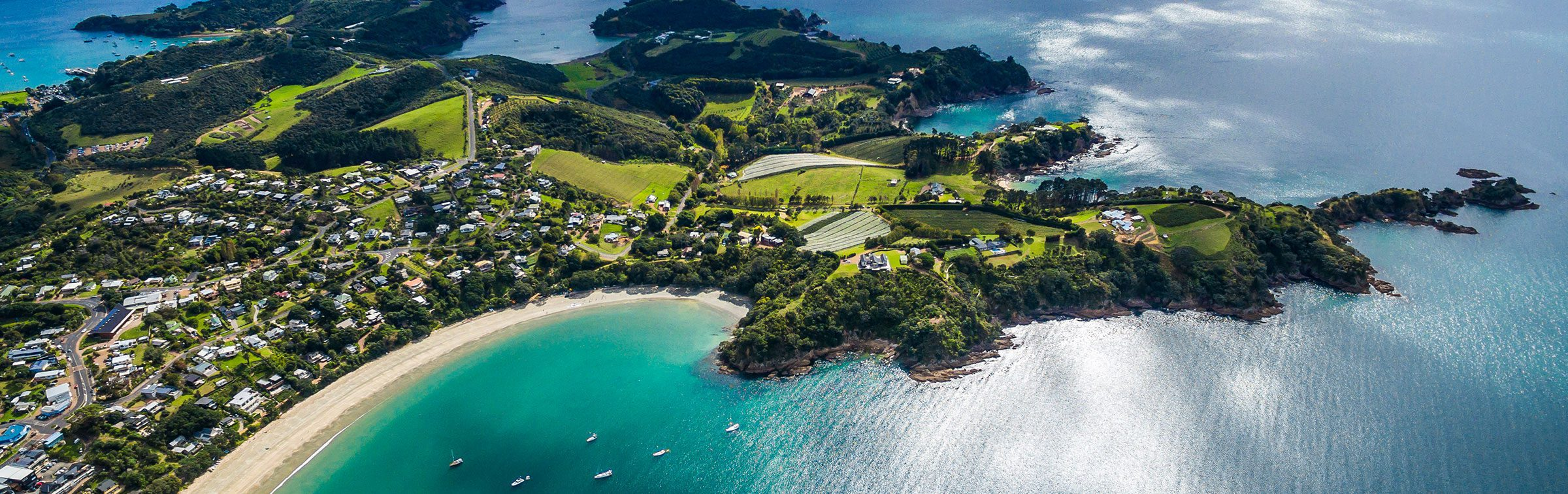 aerial view over waiheke island showing the turquoise water and green interior of the island on New Zealand tour