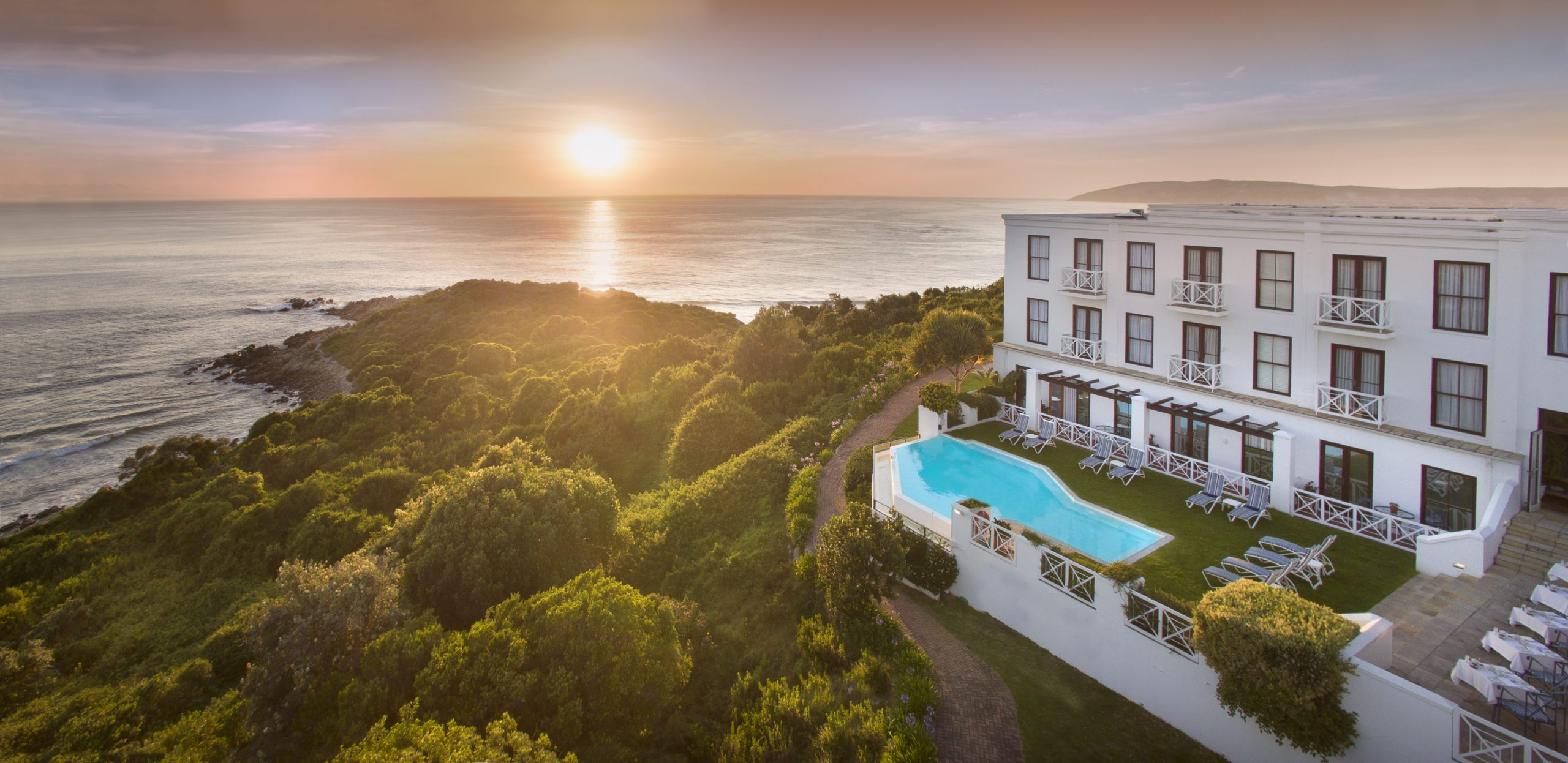 the plettenberg exterior view overlooking ocean views, lush green trees and a pretty sunset