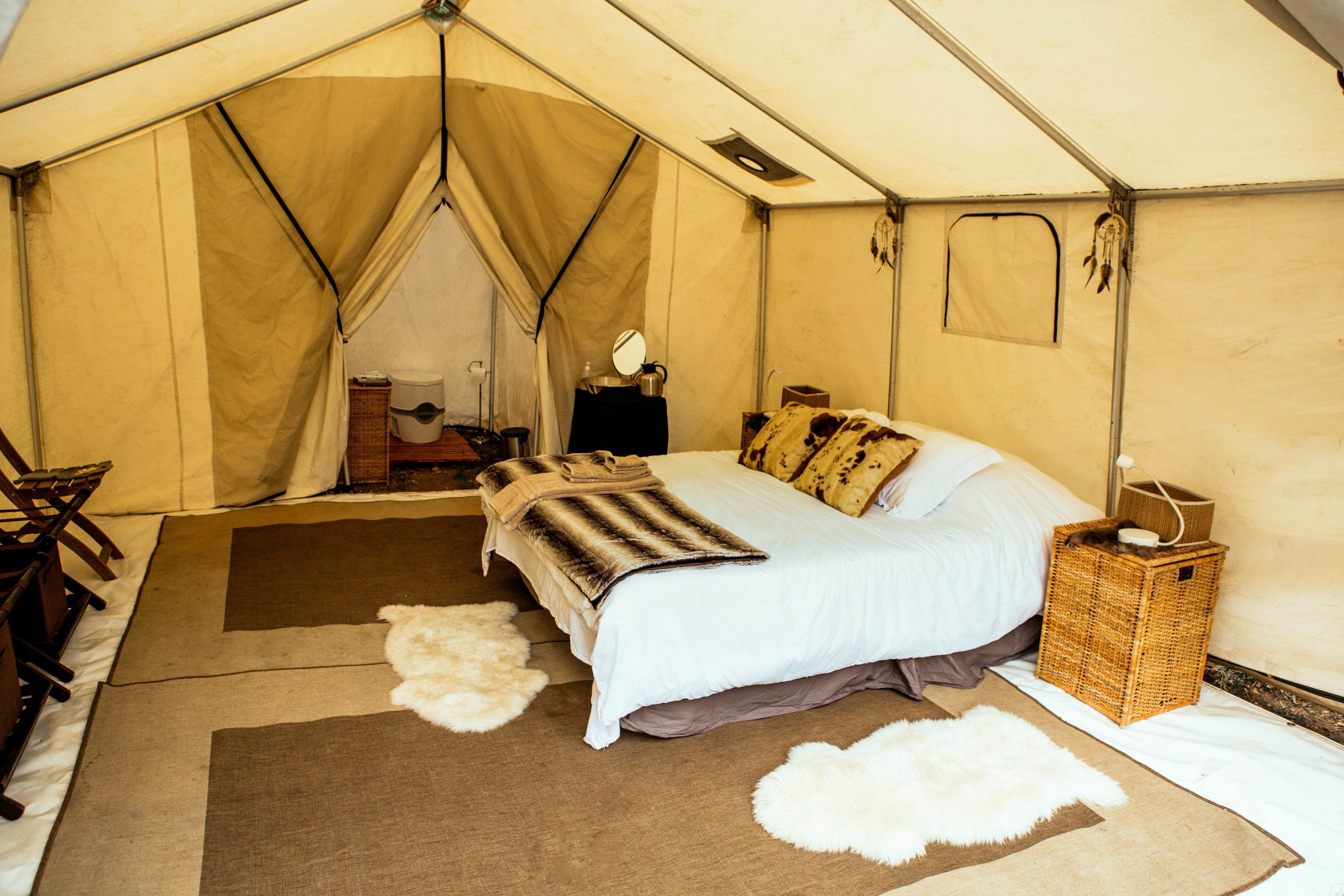 inside of a private tented camp in Yellowstone featuring white tent walls and white duvet