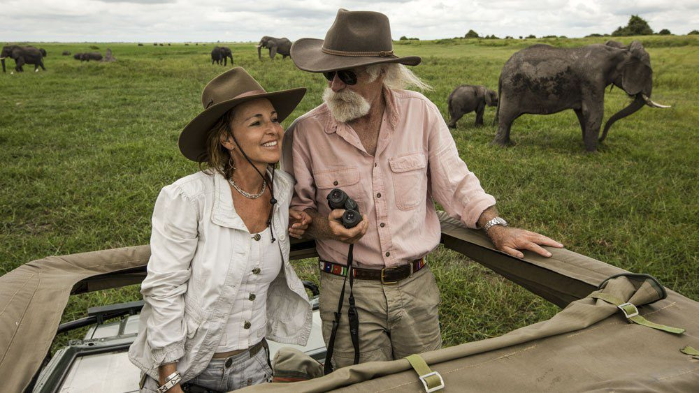 glamorous couple on safari in an open 4 x 4 vehicle