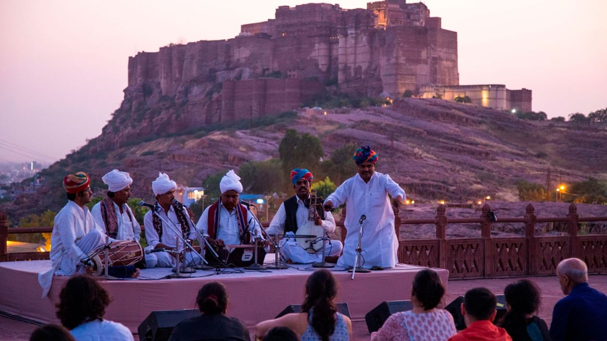 musicians in white robes perform in front of Mehrangarh Fort for Jodhpur RIFF