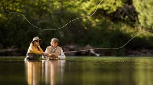 two people fly fishing in a stream