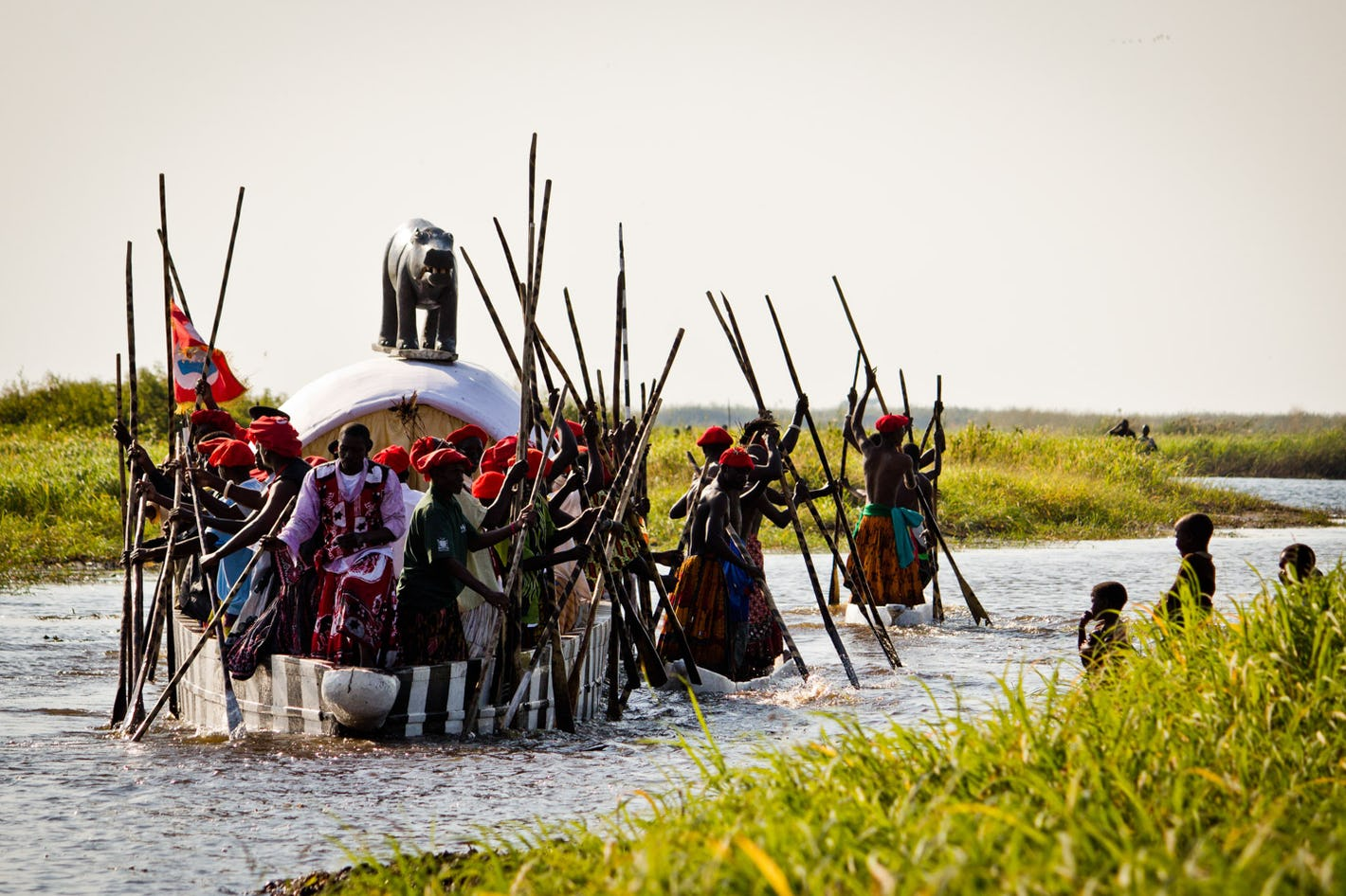polers propel a large decorated barge down a river in Zambia