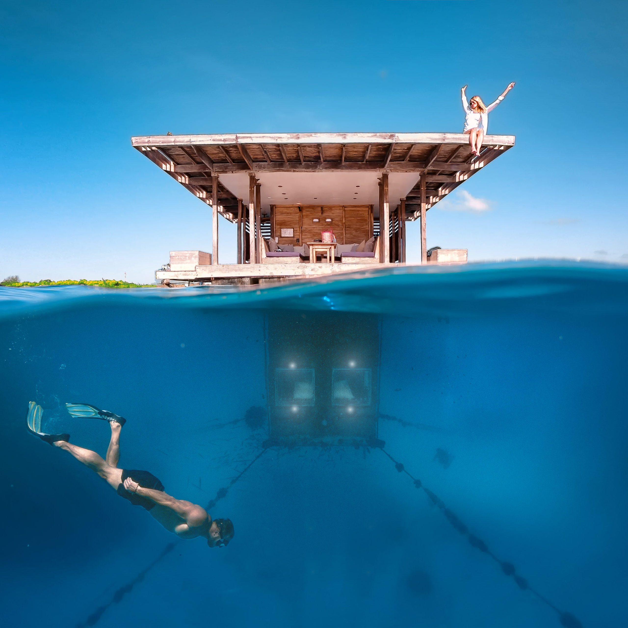 snorkeler seen below water near Manta Resort's underwater room