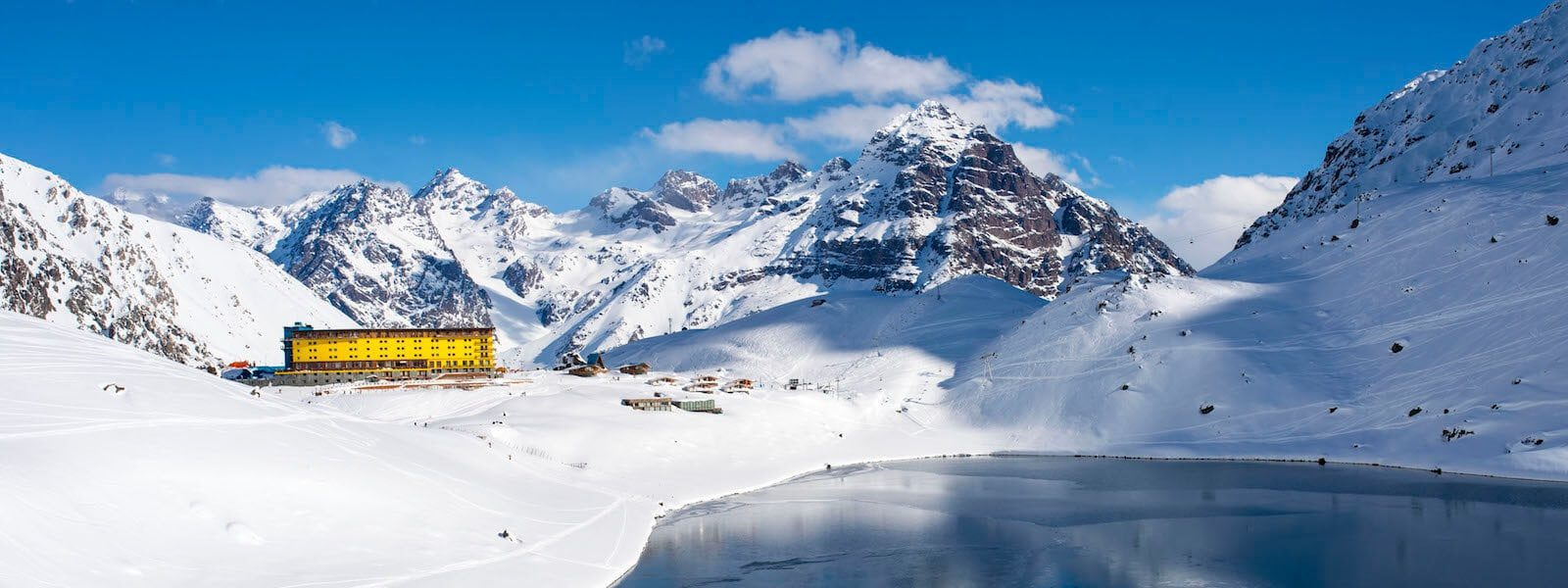 bright yellow hotel nestled in a snowy valley in the mountains of Portillo, Chile