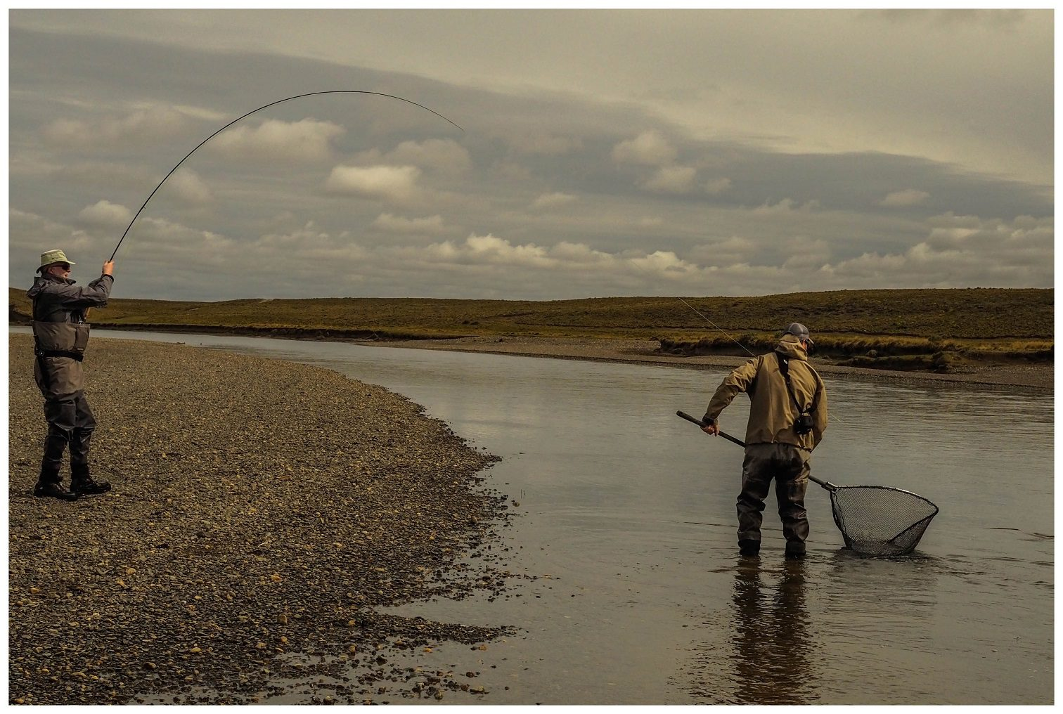 two people catching a fish in a net while flyfishing at Villa Maria Tierra del Fuego