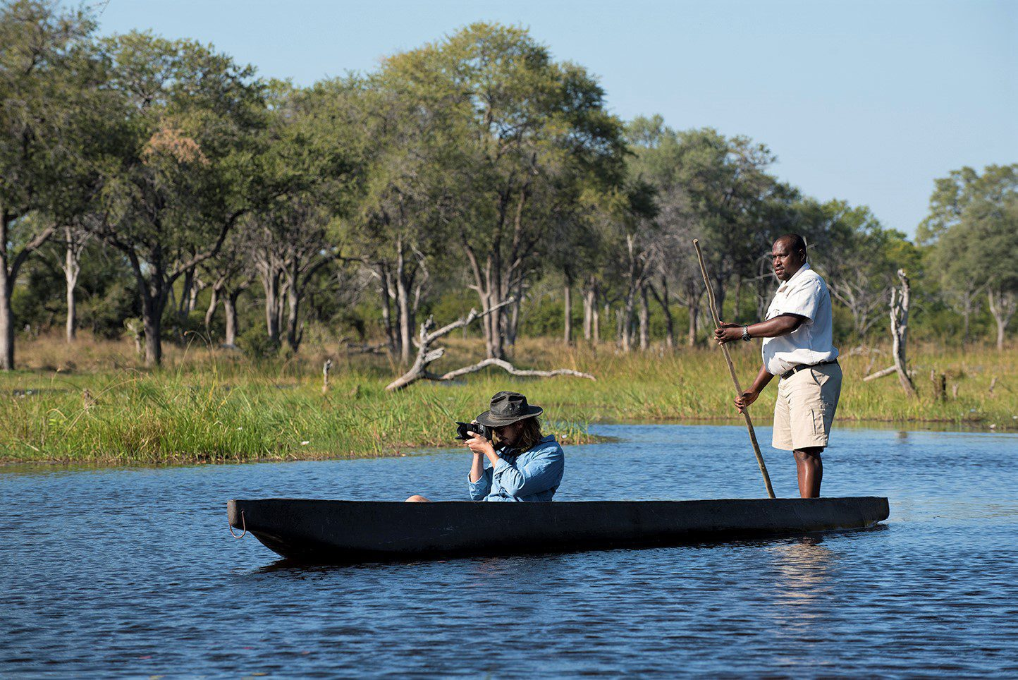 woman taking a photo on a mekoro safari at Khwai bushcamp