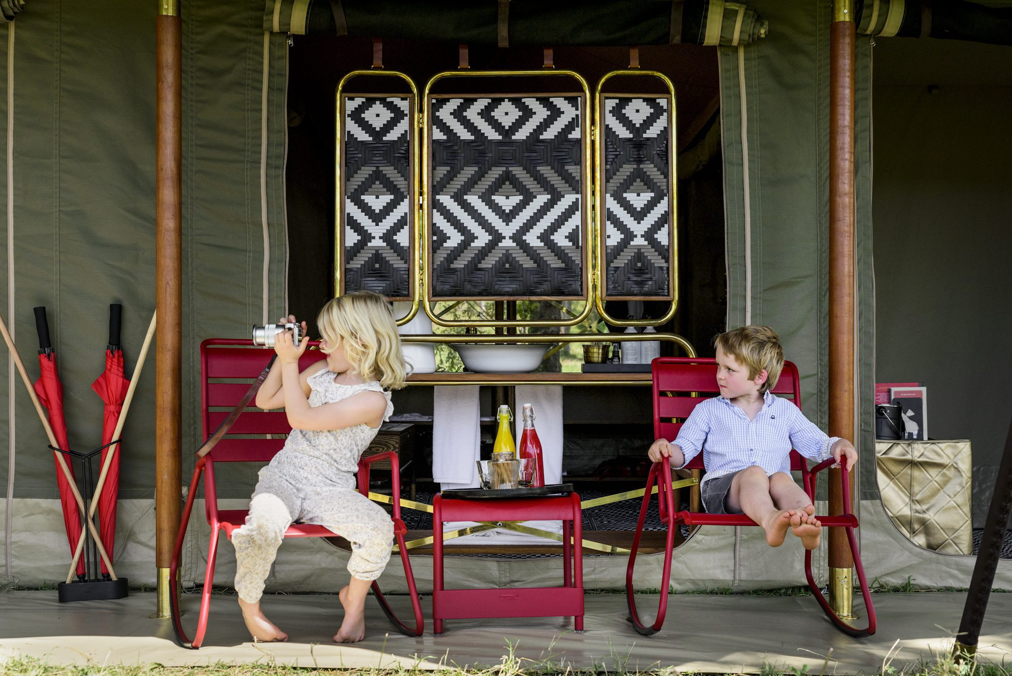 two blonde children sitting on red chairs at Angama Safari Camp looking at something in the distance