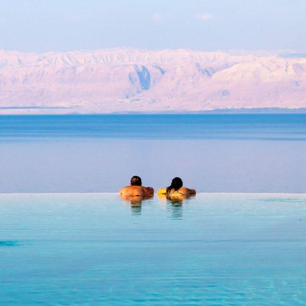 man and woman at kempinski hotel dead sea infinity pool