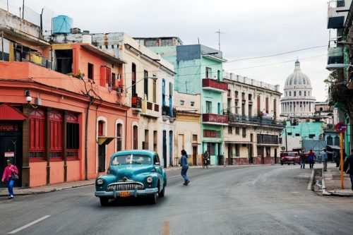 Classic blue automobile driving past worn buildings in Havana