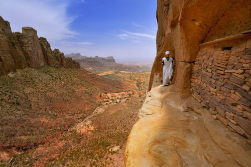 man walking along the edge of a cliff in Ethiopia